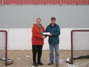 Pinawa Foundation Board Member Carol Findlay presents $1000 to Chris Elcock, Orville Acres Arena Board Chair