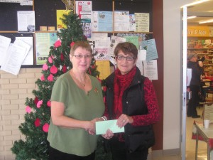 Pinawa Foundation Board Member C. Findlay presents a $350 cheque  to L Tait PSS PAC. Money goes toward the Score Board project.